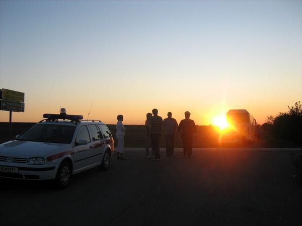 Австрийский закат. Слева направо: полицейская машина, четверо наших товарищей, суровый полицейский, яркая жёлтая звезда, второй автобус.
